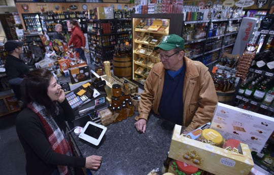 Twisted Oak Wine, Spirits and Craft Beer convenience store employee Rebecca Jendo, left, of Troy, shares a laugh with regular customer Carl Peterson, right, 81, of Rochester Hills.