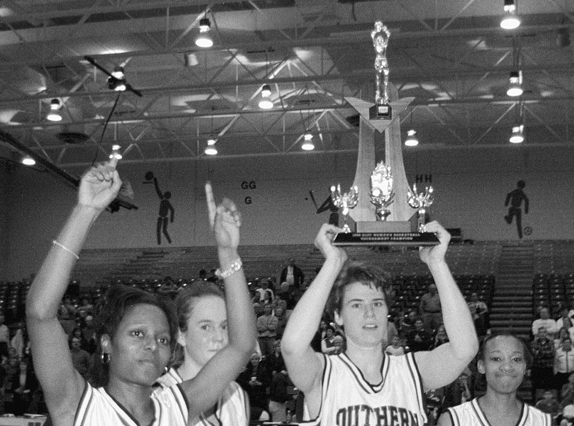 Eileen Weber celebrates the 1998 GLVC conference title with teammates.
