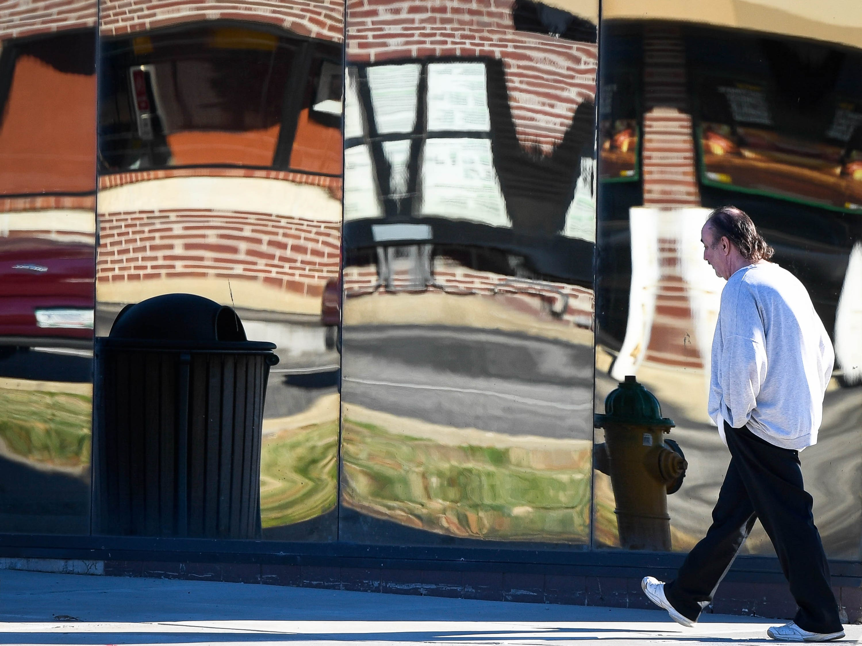 Sun and warming temperatures coaxe people outside like Daniel Creech, Evansville, walking by a mirrored building front on Virginia Street Monday afternoon, December 17, 2018.