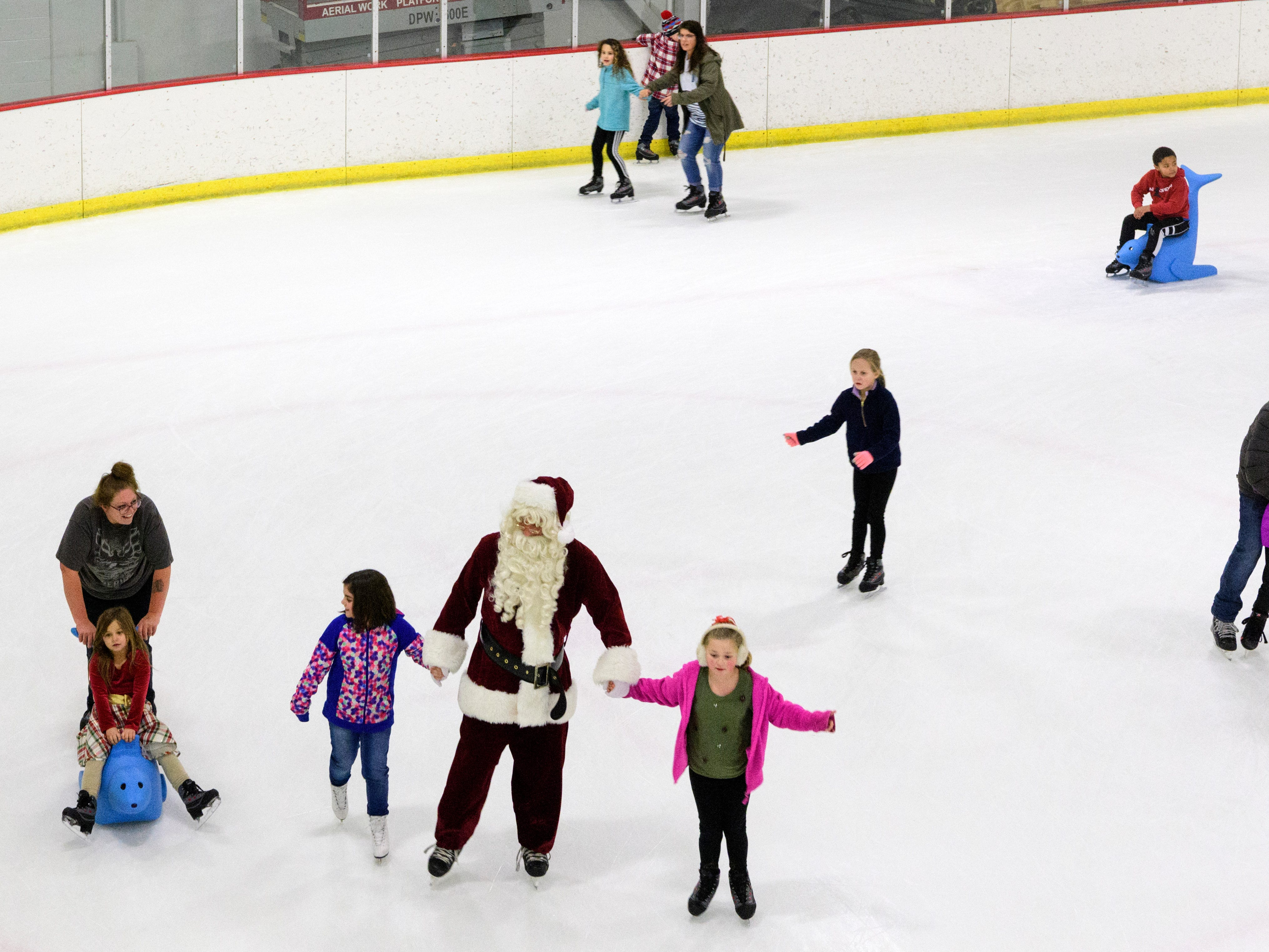 """Adelyn Ward, left, and Calea Reynolds, right, glide past other ice skaters as they hold hands with Santa during the ninth annual """"Skate with Santa"""" event at Swonder Ice Arena in Evansville, Ind., Sunday, Dec. 16, 2018. A portion the event's proceeds were donated to Autism Evansville, a local non-profit resource center for families with children on the autistic spectrum."""