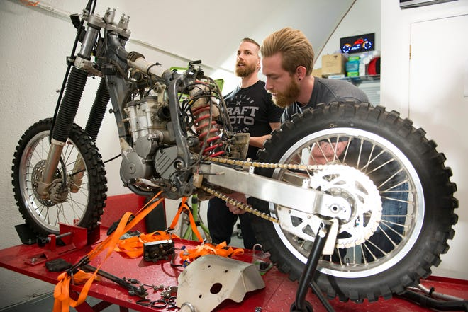 Brothers Caleb and Cody Knobel of Craft Moto work to dismantle a bike before transforming it with their own design at their shop on Jefferson Street on Friday, Dec. 14, 2018.