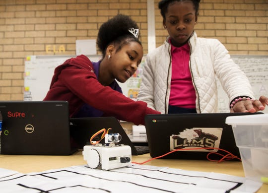 Lehigh Acres middle school students, Geurlande Lume and Faith Justima code a robot in the FUSE class on Monday. The program allows students to create science, technology, engineering, arts and mathematics related projects.