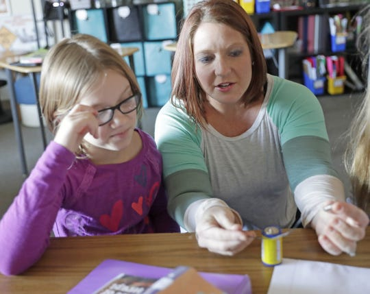Teacher Megan Zavernik works with student Megan Christnovich on a science project on electricity during class Nov. 19 at Forest Glen Elementary School in Suamico.