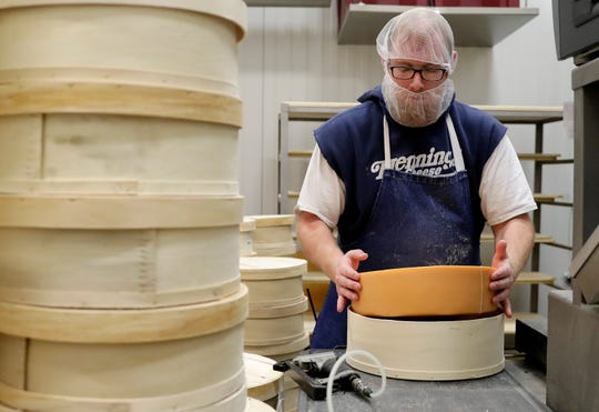 Henning's Wisconsin Cheese employee Sean Pingel packages wheels of cheese Nov. 29 at the plant in Kiel.