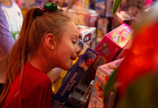 "Brayden Dame, 7, uses her nose to push buttons on a toy she has chosen in ""Santa's Workshop"" at Shriners Hospitals for Children in Greenville Wednesday, Dec. 12, 2018."