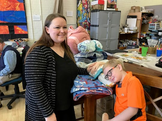 Codie and Jude Sheppard with a stack of blankets for A Hug from Heaven at the West End Co-Op