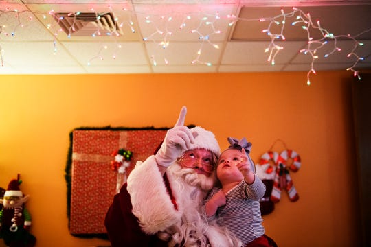 Hattie Williams, 1, points up at Christmas lights hanging on the ceiling as she is held by Santa Claus at Shriners Hospitals for Children Greenville on Monday, Dec. 17, 2018.