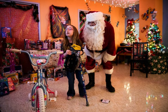 Mary Goodman, 8, shows Santa Claus her new bicycle at Shriners Hospitals for Children Greenville on Monday, Dec. 17, 2018.