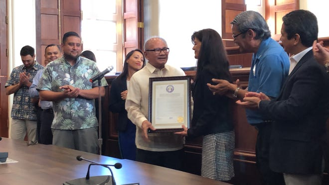Dr. Aurelio Espinola, wearing white, receives a resolution from the Guam Legislature, recognizing him for 25 years as the island's chief medical examiner on Monday, Dec. 17, 2018 in the Guam Congress Building public hearing room in Hagåtña. Espinola, 78, will retire at the end of January 2019 and will move to the Philippines.