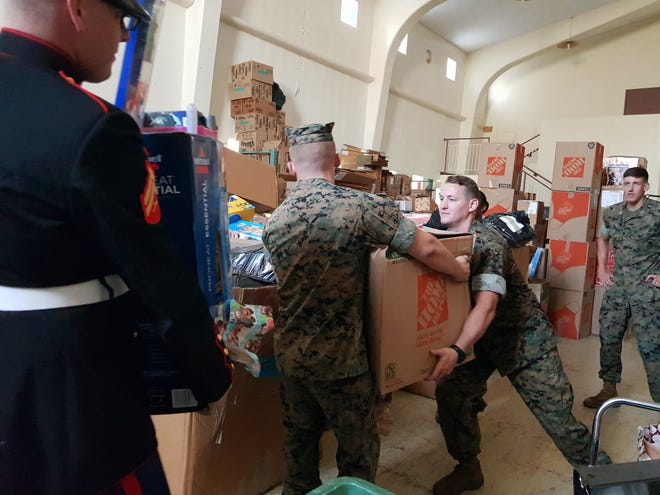Marines help unload a container full of toys at the Salvation Army in Tiyan as part of the Marine Toys for Tots program on Dec. 17, 2018.