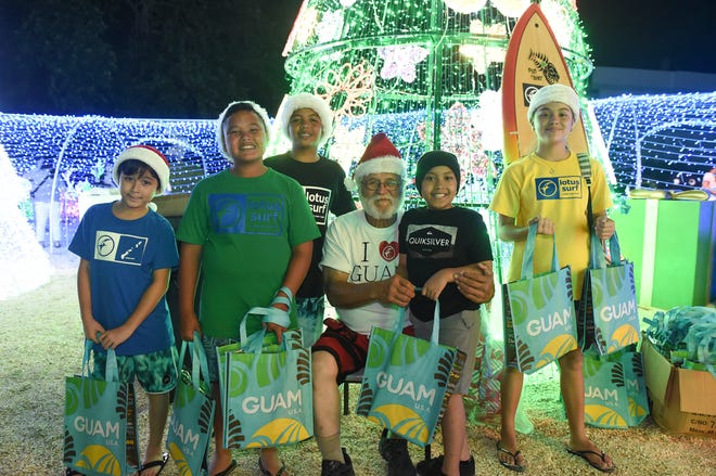 "Gabriel Roby, 8, second from right, poses for a picture with ""Island-style"" Santa and his elves at the Guam Visitors Bureau's Christmas Village in Tumon, Dec. 17, 2018."
