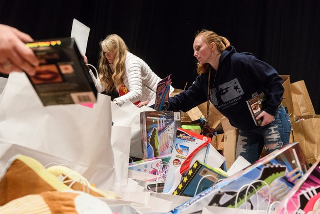 Briana Duncan, 16, from right, Jamee Leigh and Brittany Wolney organize large gift bags full of hygiene products and toys for children, ages 4-11, attending the Goodfellows Christmas party at South Middle School in Henderson, Ky., Sunday, Dec. 16, 2018.