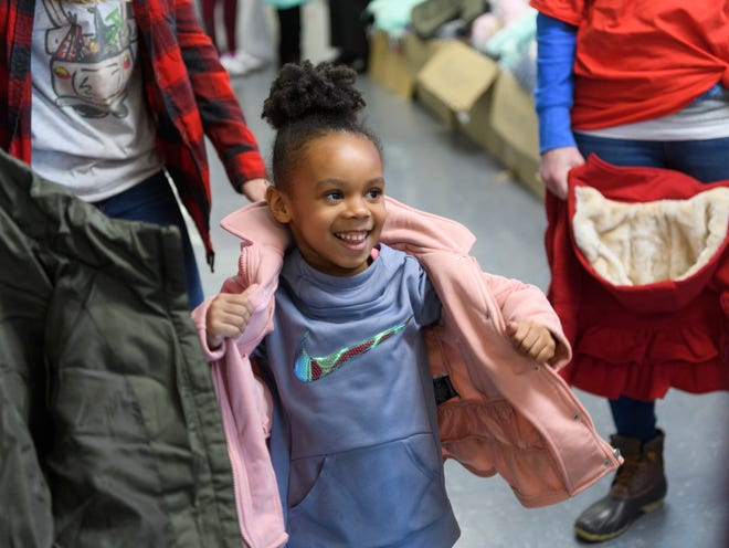 Rasheiona Joseph, 5, tries on a brand new coat as volunteers praise how good she looks in it during the Goodfellows Christmas party at South Middle School in Henderson, Ky., Sunday, Dec. 16, 2018. After getting their picture taken with Santa Claus, more than 600 children ages 4-11 received a new coat from J. C. Penney, a large bag of toys and other goodies to take home.