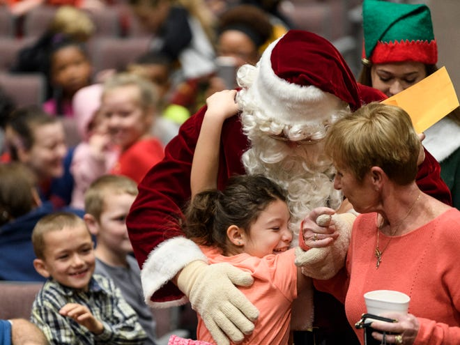 Carmen Sedillo, 8, latches onto Santa Claus as Phyllis Pendergraft, right, leads him to the stage to begin taking pictures with all the children in attendance at the Goodfellows Christmas party held at South Middle School in 2018.