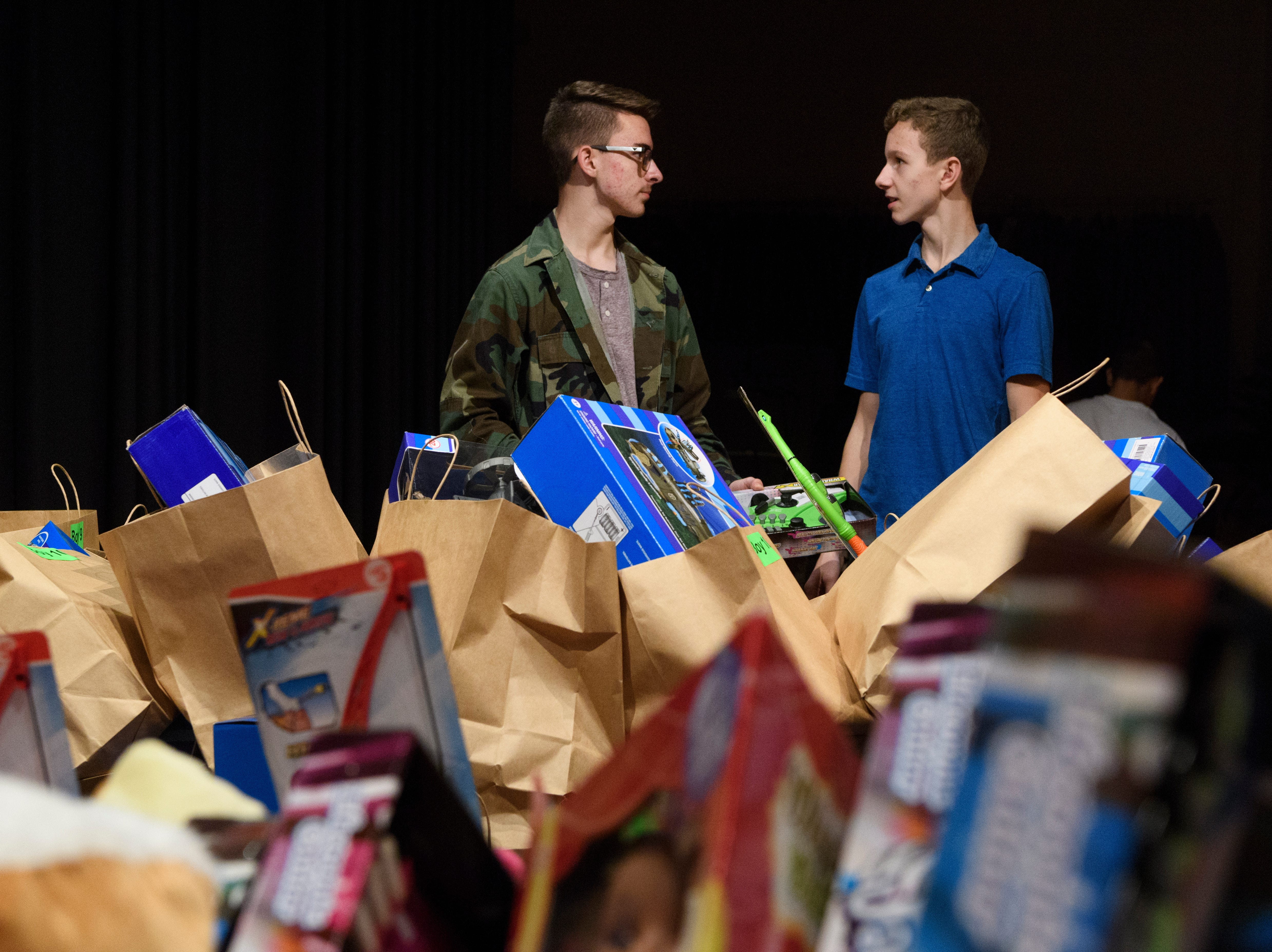 Dayton Spille, left, and Blain Krampe, right, both 15, organize bags full of toys for children, ages 4-11, to give out during the Goodfellows Christmas party at South Middle School in Henderson, Ky., Sunday, Dec. 16, 2018.