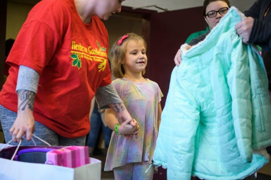 Volunteer Brittany Pompell, left, leads Ariana Sandefur, center, to another volunteer who sizes her into a new coat during the Goodfellows Christmas party at South Middle School in Henderson, Ky., Sunday, Dec. 16, 2018. This year, each child received a brand new coat from J.C. Penney.