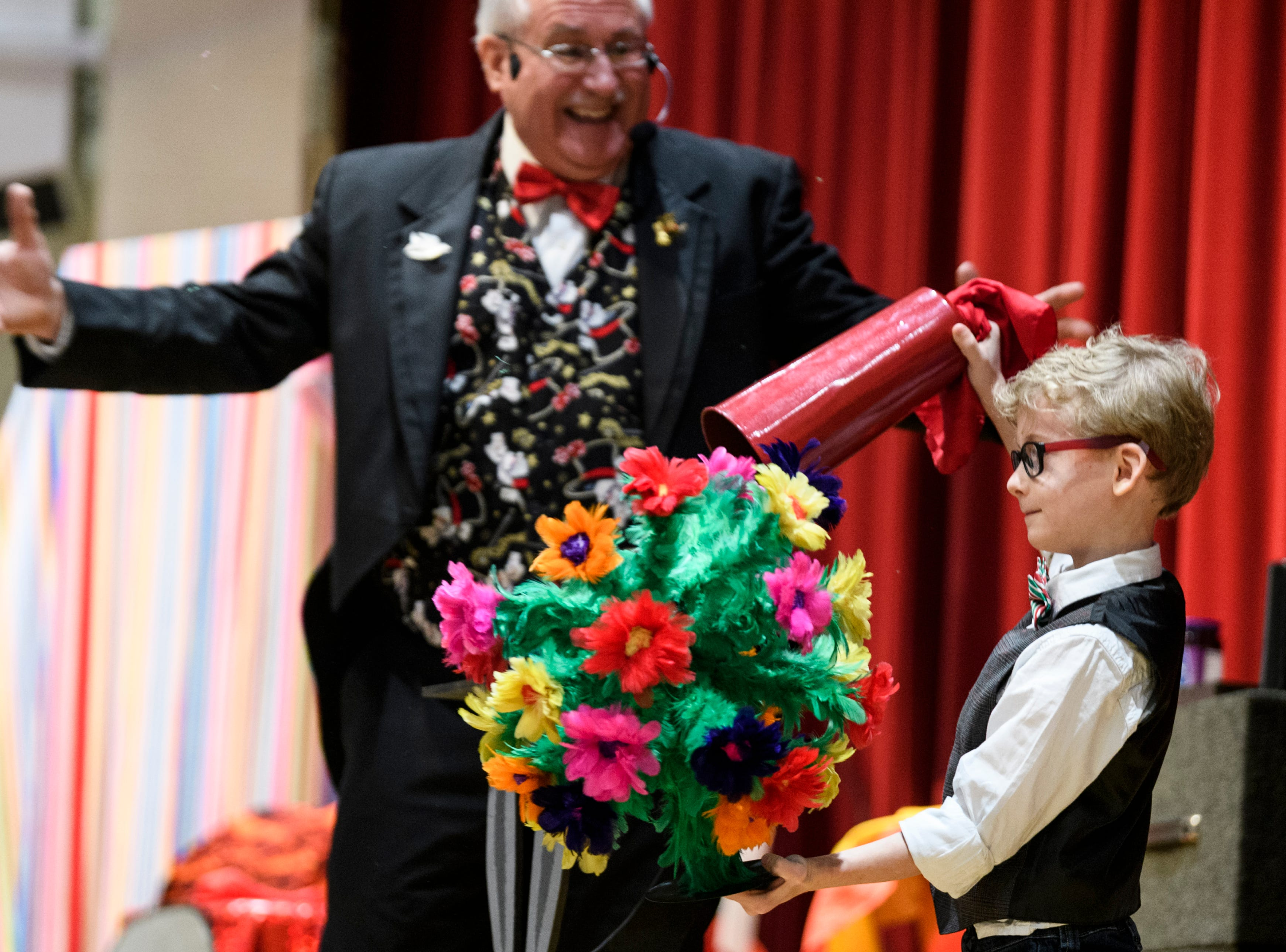 Oliver Sokeland, 7, pulls flowers out of an empty tin as he performs magic tricks with Joe DiVietro, back, known on stage as Joey D, during the Goodfellows Christmas party at South Middle School in Henderson, Ky., Sunday, Dec. 16, 2018.