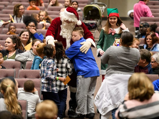 Zander Oakley, 14, center, and other children flock to Santa Claus as he arrives to the auditorium for pictures during the Goodfellows Christmas party at South Middle School in Henderson, Ky., Sunday, Dec. 16, 2018. More than 600 children were invited to attend the annual Christmas party, where they watched magic and puppet shows, took portraits with Santa and received large bags full of toys and clothing.