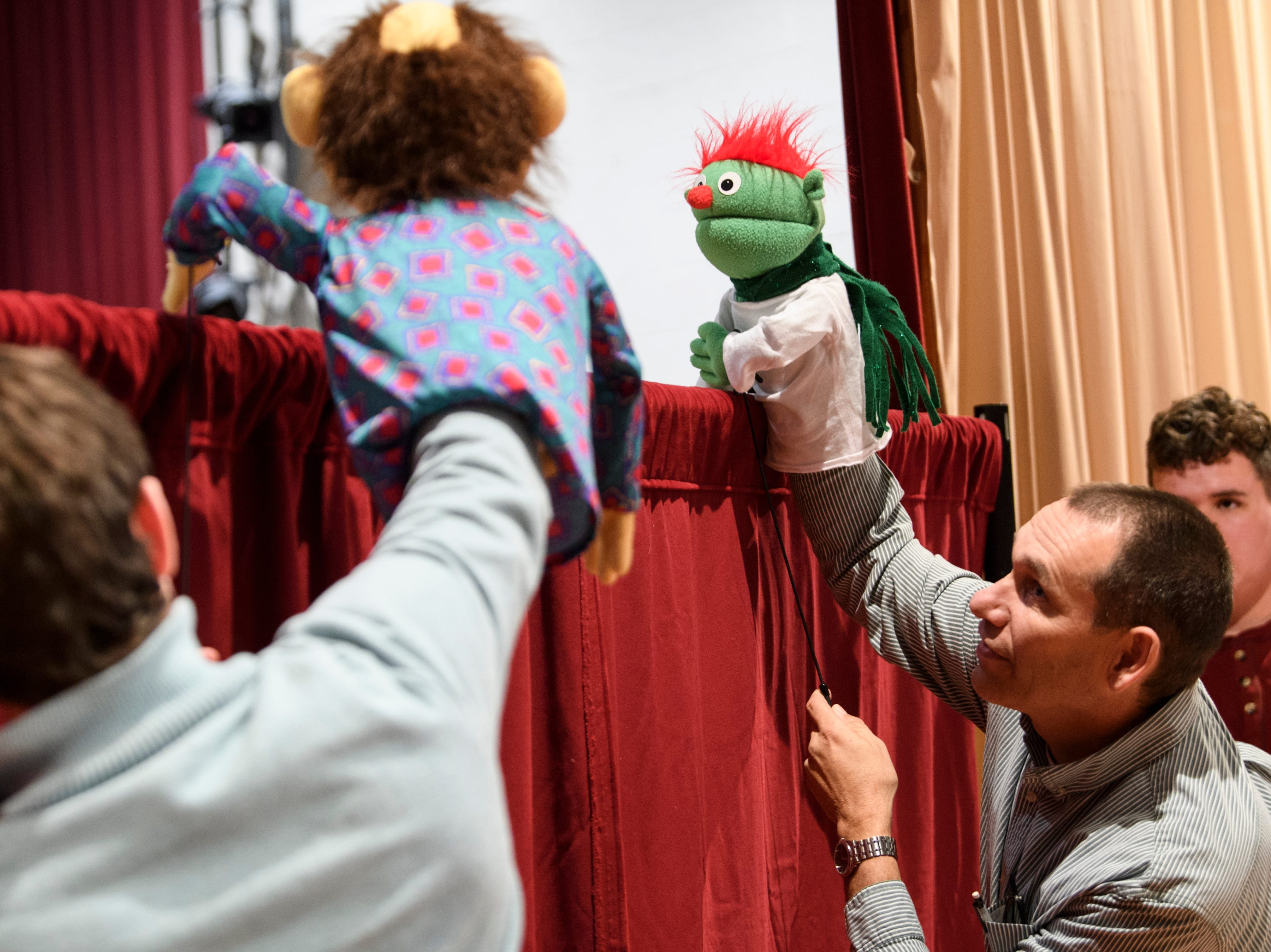 Ben Dalton, left, and Jim Bryan, right, put on a puppet show for children attending the Goodfellows Christmas party at South Middle School in Henderson, Ky., Sunday, Dec. 16, 2018.