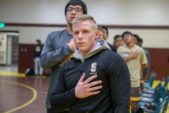 Speedway Sparkplugs' Riley Walker puts his hand over his heart while saying the Pledge of Allegiance before the match against the Cascade Cadets at Speedway High School on Tuesday, Dec. 11, 2018.