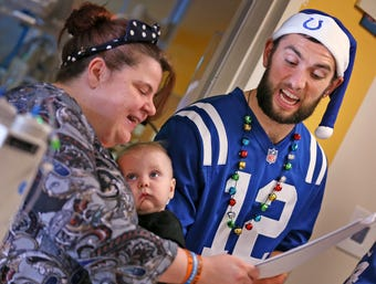 Colts players and cheerleaders try to harmonize for the holidays, caroling for patients at Riley Hospital for Children.