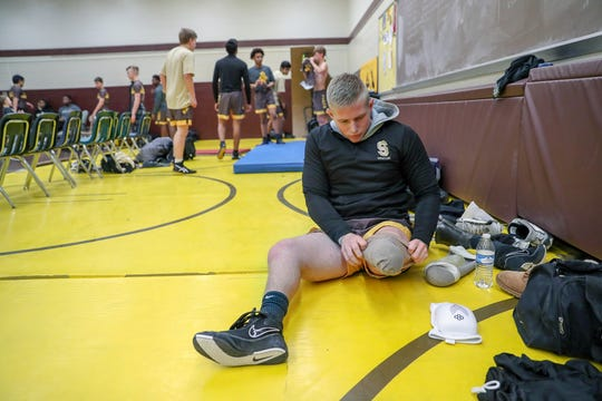 Speedway Sparkplugs' Riley Walker takes off his left leg prosthetic before warming up for the team's wresting match against the Cascade Cadets at Speedway High School on Tuesday, Dec. 11, 2018.