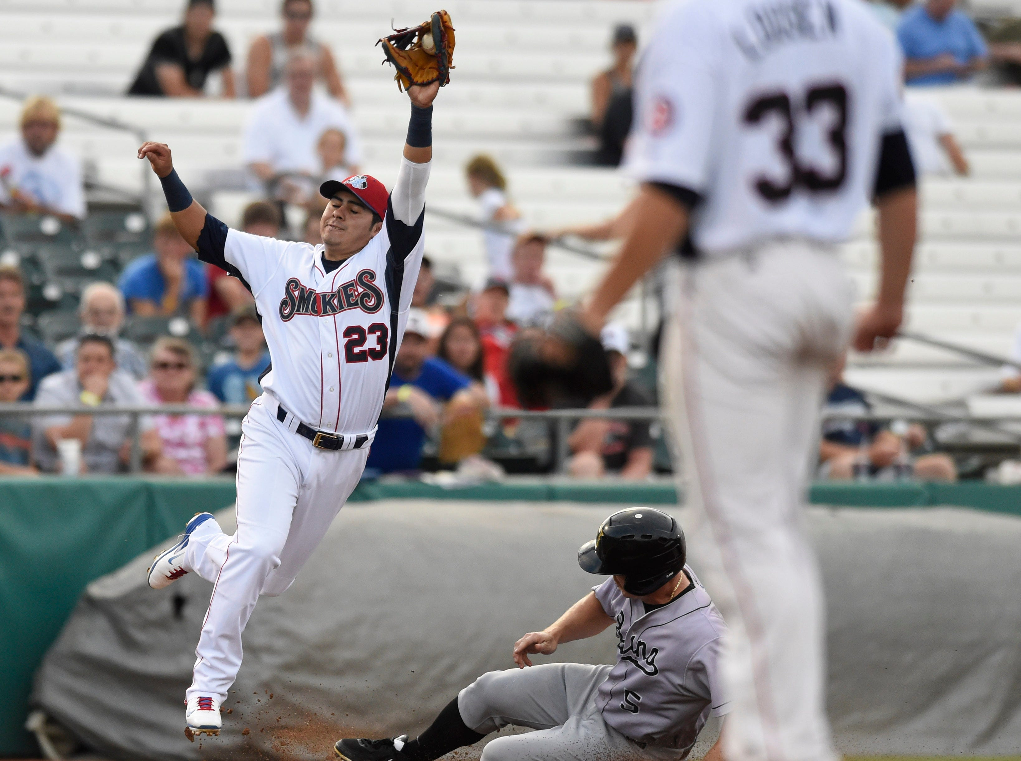 Jacksonville Suns' Joe Benson (5), center, steals third base as Tennessee Smokies third baseman Christian Villanueva (23), left, leaps for the catch during a baseball game at Smokies Park in Knoxville on Thursday, July 10, 2014.