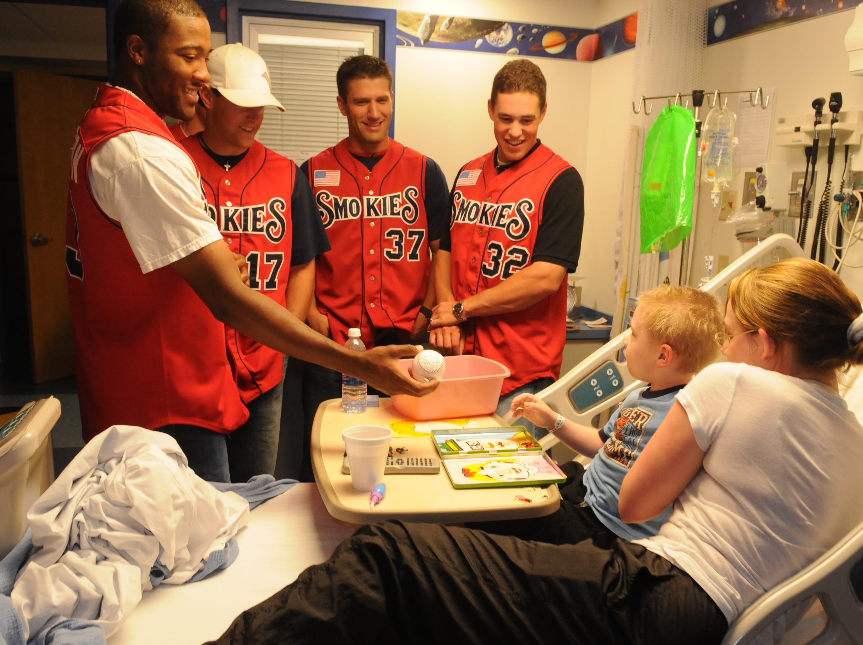 Davyn Mengeling, 4, and his mother Stephanie Mengeling, right,  get a autographed baseball from Tennessee Smokies baseball players, #13 Jay Jackson, left, #17 Casey Coleman, #37Russ Canzler, and #32 Blake Lalli.   The players were visiting Children Hospital with their Coach Ryne Sandberg and his wife Margaret Sandberg Wednesday morning. Baseball player for the Knoxville Smokies team and manager Ryne Sandberg visited Children's Hospital on  Wednesday, May 27, 2009