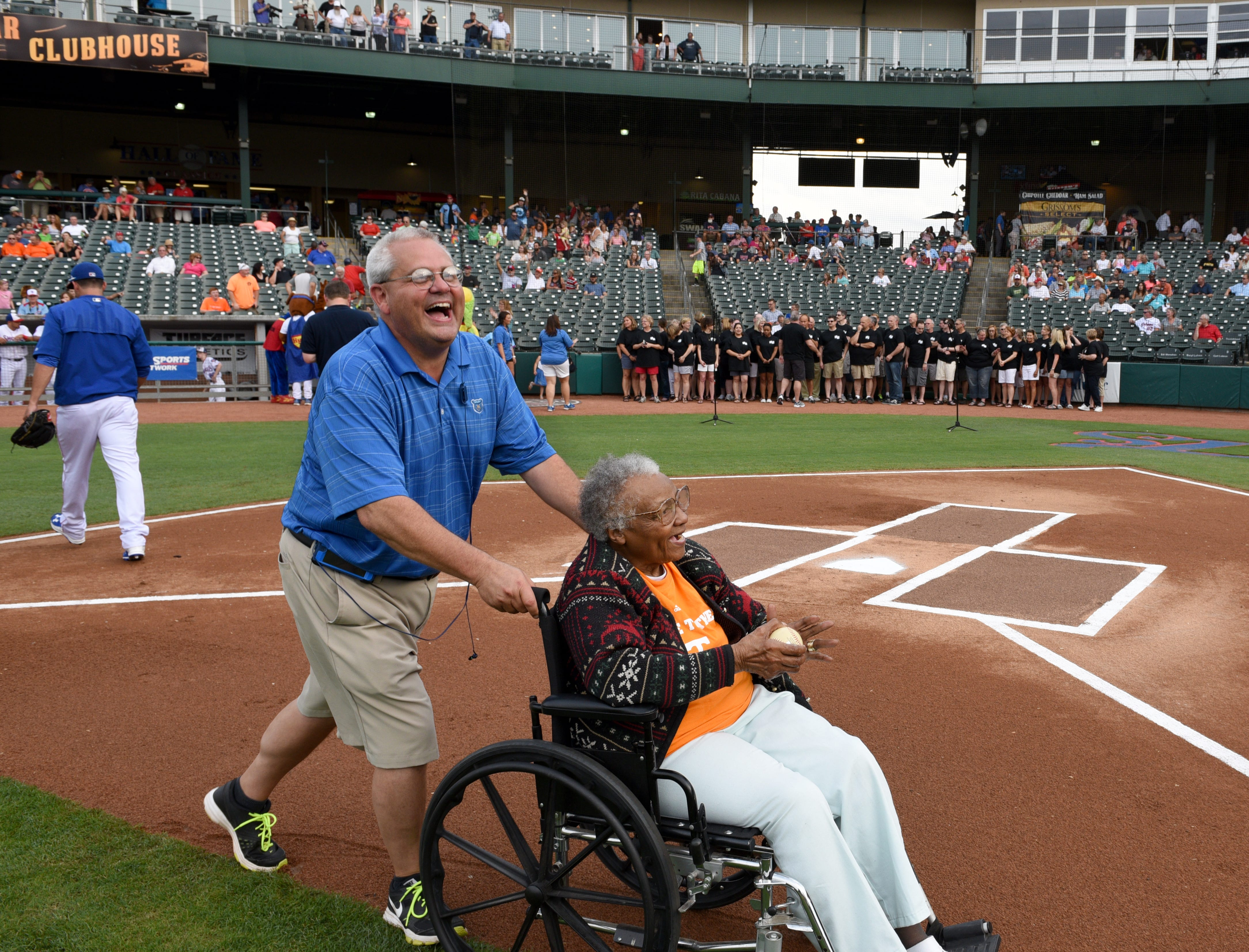 Craig Jenkins laughs hearing Helen Turner, co-founder of the Love Kitchen, say she was shocked she got to keep the ball she threw out to start the Tennessee Smokies baseball game against the Mississippi Braves Thursday, Jun. 18, 2015.  The game was nationally televised by CBS Sports Network.