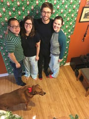 From left Eric Lam and wife Mary Duckett, Sean Britt and wife Cassidy Duckett Britt, Christmas 2017. They're posing for a photo in front of the paper that covers the opening where gifts are in the home of Randall and Maryellen Kennedy Duckett. The Ducketts began wrapping the opening in 1995 when their daughters were young; the tradition continues.