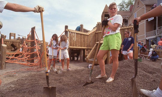 Nicole Fleming helps spread gravel on the playground surface at Fort Kid, April, 1991.