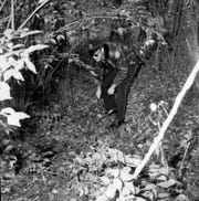 Knoxville Police Department Officer Tom McDonald looks for evidence near the Rose Busch home on Nov. 20, 1968, the morning after the murder.