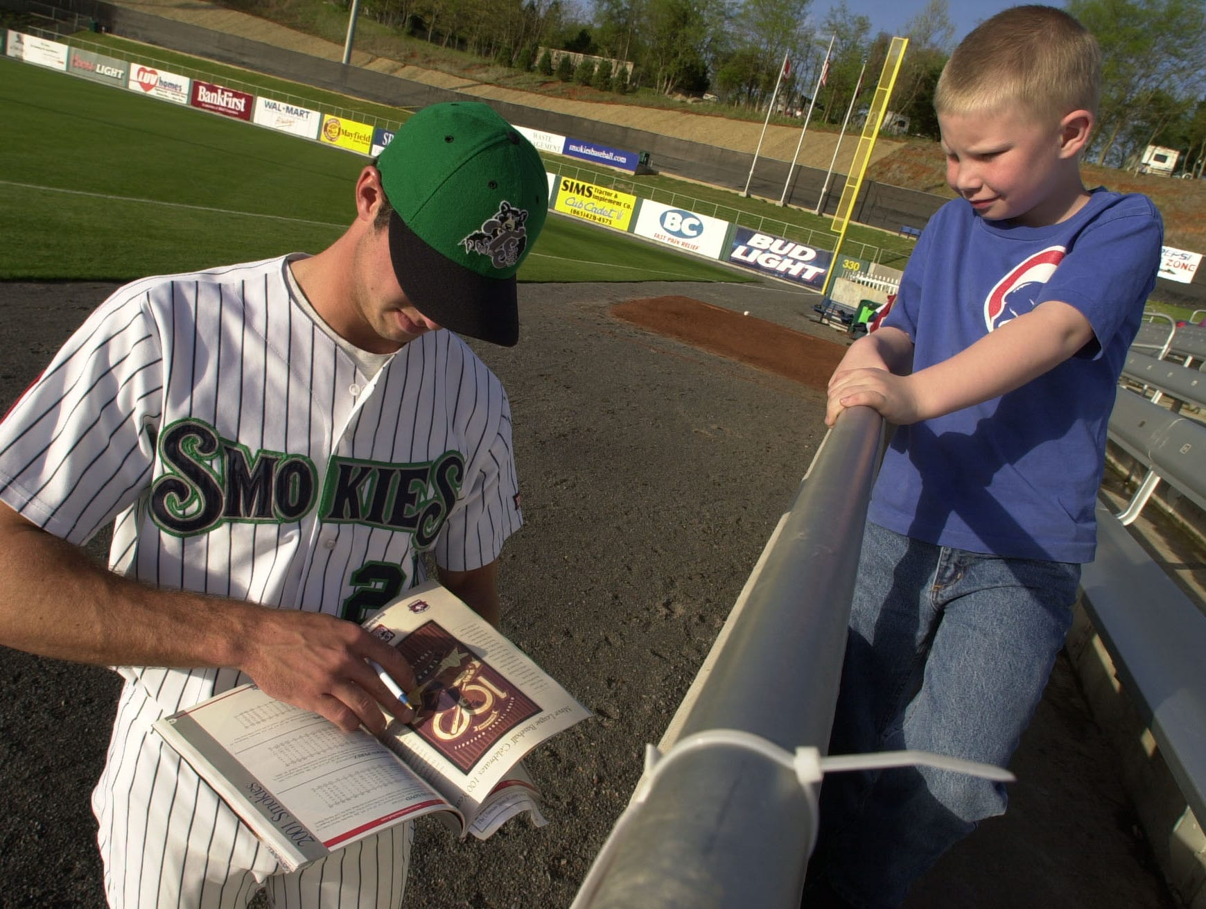 Tennessee Smokies' Josh Phelps signs an autograph for seven-year-old fan Casey Henry just prior to the season's opening game against Chattanooga Friday evening.