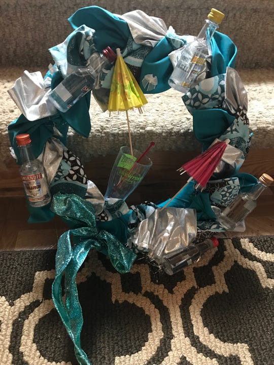 This wreath has shown up at Charlotte Jensen's regifting party for several years. It has been decorated with airplane bottles of liquor to make it more enticing.