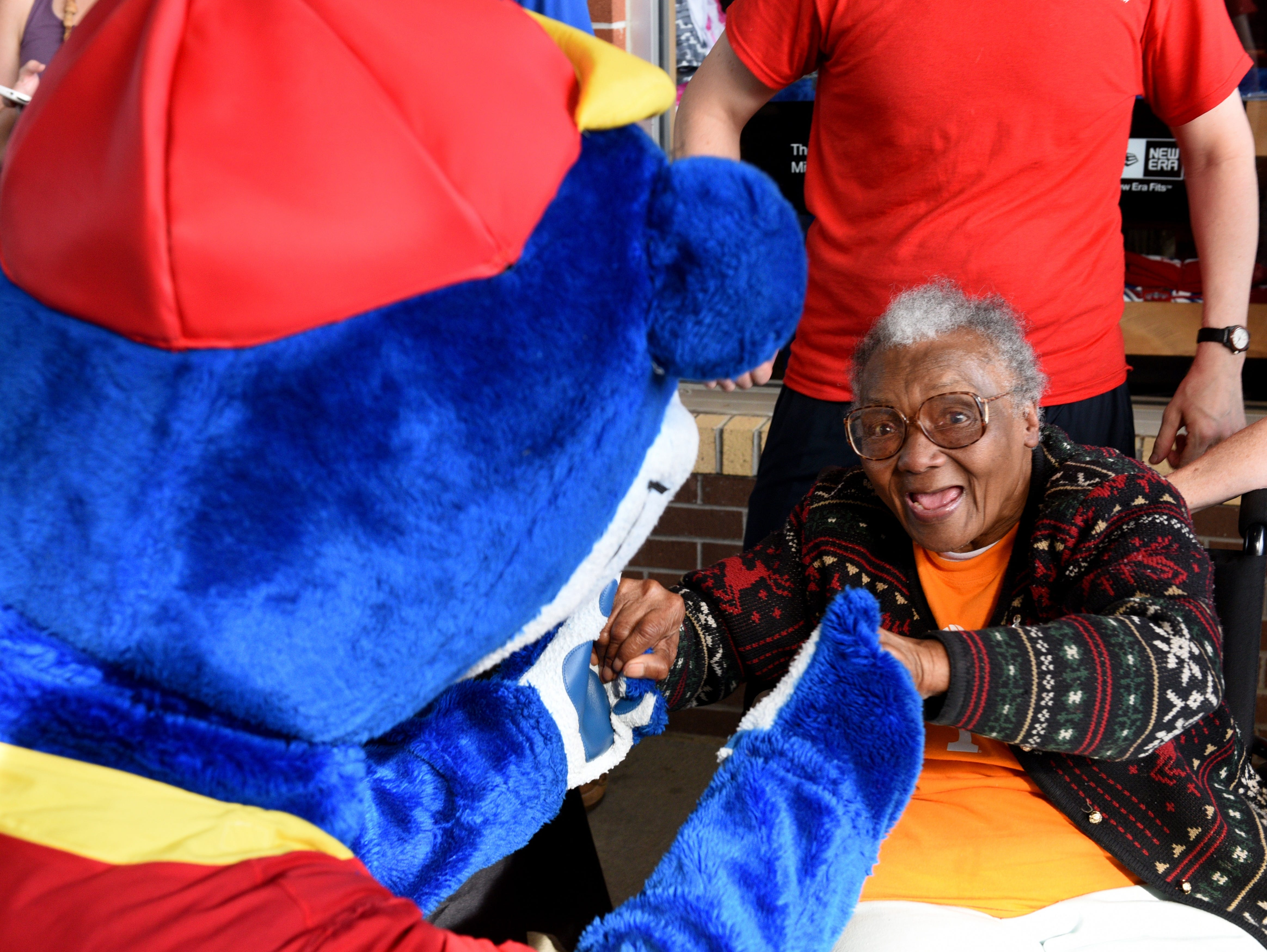Helen Turner, co-founder of the Love Kitchen, greets the mascot before throwing out the first pitch at the Tennessee Smokies baseball game against the Mississippi Braves televised by CBS Sports Network Thursday, Jun. 18, 2015.