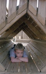 Christian Neveu takes a break from the sun inside a wooden tunnel at Fort Kid, January, 2000.
