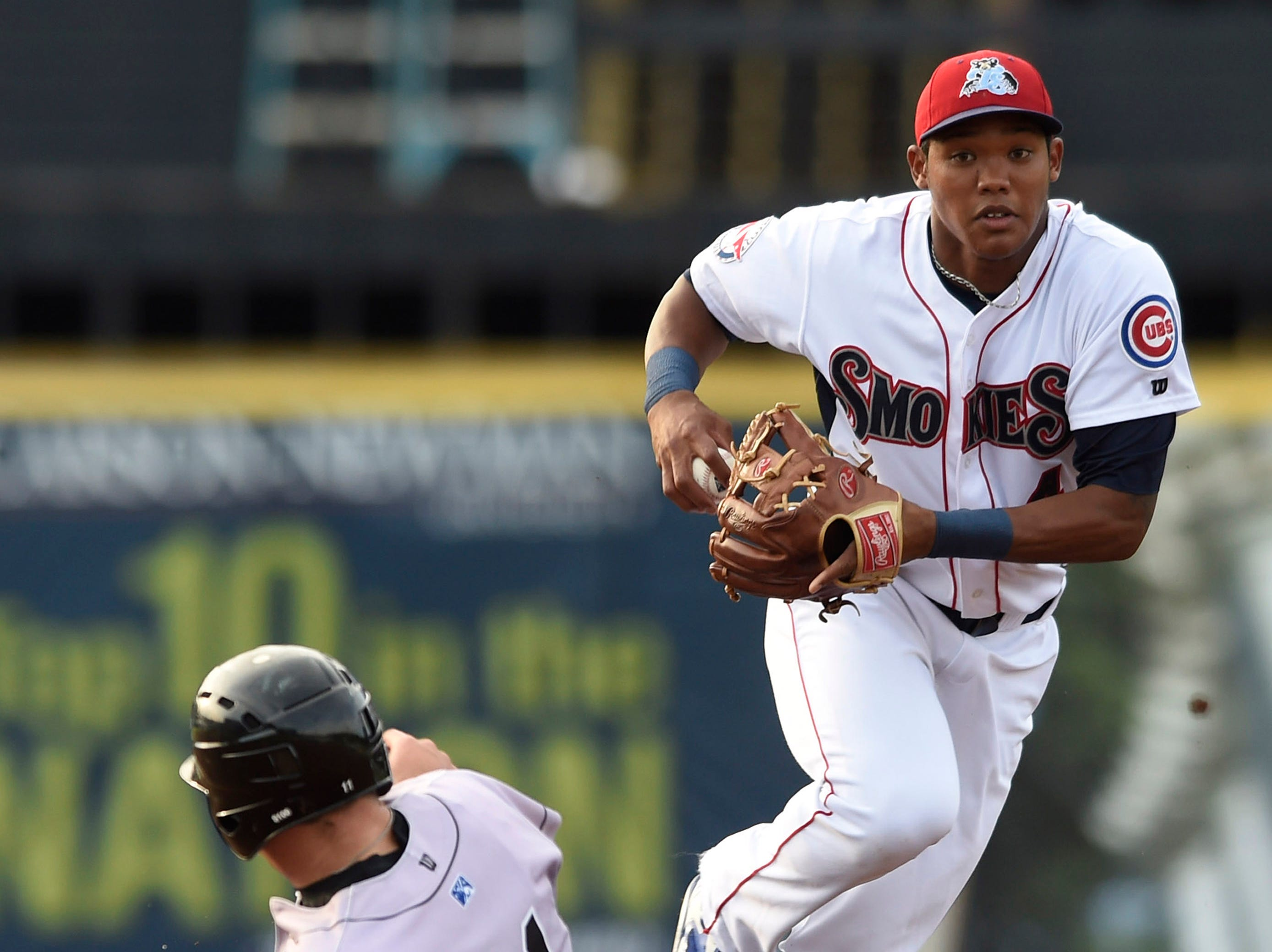 Tennessee Smokies shortstop Addison Russell (4), right, gets Jacksonville Suns catcher J.T. Realmuto (11) out at second base before throwing to first for a double play during a baseball game against at Smokies Park in Knoxville on Thursday, July 10, 2014.