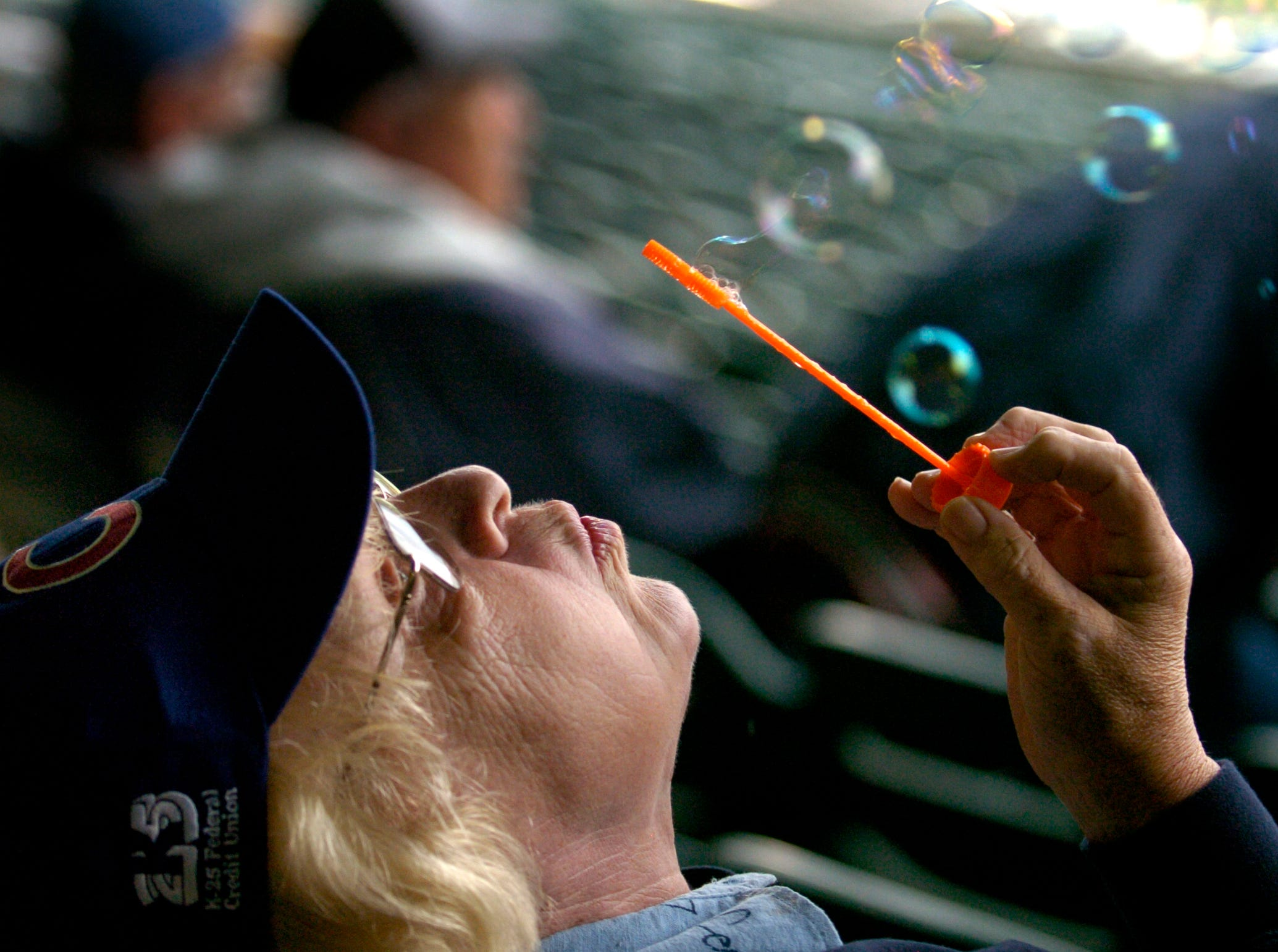 """Dorothy Gilbert blows bubbles during a rain delay at the Tennessee Smokies home opener Wednesday in Sevierville. The Smokies game against the Huntsville Stars was postponed and will be made up as part of a double-header on Thursday night. Gilbert was philosophical about the weather. """"You have to bring your own fun,"""" she said."""