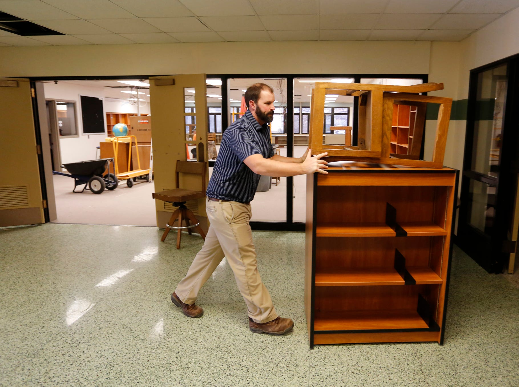 Building Commissioner Chad Spitznagle pushes a cabinet and chairs down a hallway as the City of West Lafayette moves its offices from the Morton Center into the former Happy Hollow School Monday, December 17, 2018, in West Lafayette. The city will keep it's offices in Happy Hollow for two years while the Morton Center is being renovated. The city will move its offices back to the Morton Center when renovations are completed.