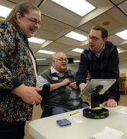 Jane Hanley, left, deputy director of the Fairfield County Board of Elections, laughs with Fairfield County Commissioner Mike Kiger, center, and Fairfield County Clerk of Courts Brandon Meyer, as she shows them how the board's new electronic poll books work in this March 9, 2016, file photograph.