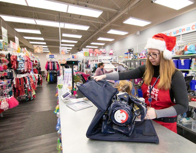 Shirley Williams, co-owner of Once Upon a Child, folds a Pack 'n' Play Monday, Dec. 17, 2018, one of thousands of items sold to the Brighton store for resale.