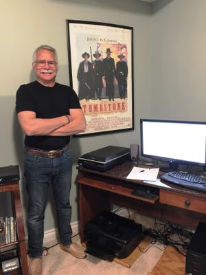 "Author John Farkis stands near his writing desk in his Green Oak Township home. His new book ""The Making of Tombstone: Behind the Scenes of the Classic Modern Western"" is about how the film was made and the history of the notorious town."
