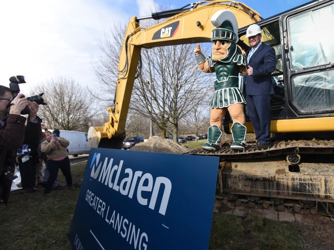 Kirk Ray, right, president and CEO of Mclaren Greater Lansing, poses for a picture with Sparty, Monday, Dec. 17, 2018, at the McLaren Greater Lansing groundbreaking just north of Collins Rd.  Also pictured is photographer David Trumpie.  The new health care campus will include a 240-bed hospital,  cancer center, and medical services building.