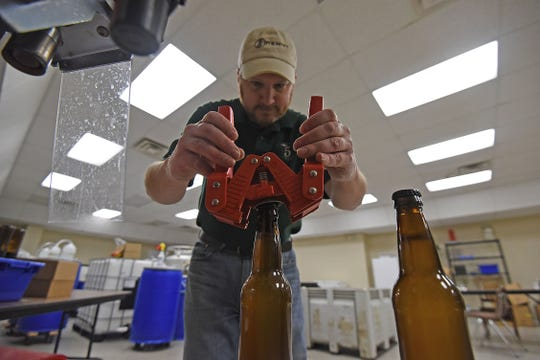 Josh Beard puts a cap on a bottle of 5 Penny Cider on Monday.