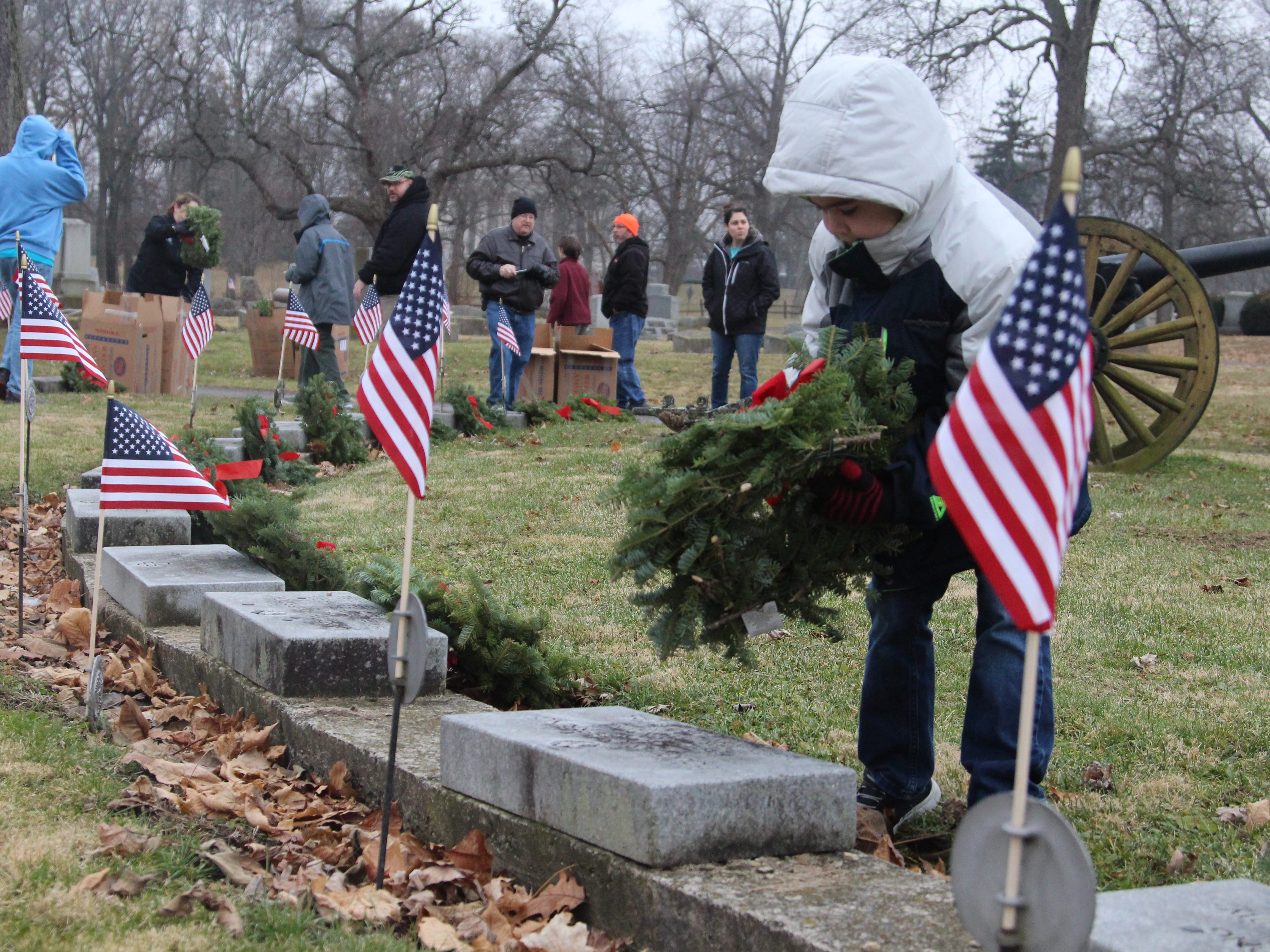 Volunteers place wreaths at the foot of veterans' grave sites Saturday at Marion Cemetery for Wreaths Across America, a nationwide effort to honor veterans at the holiday season.