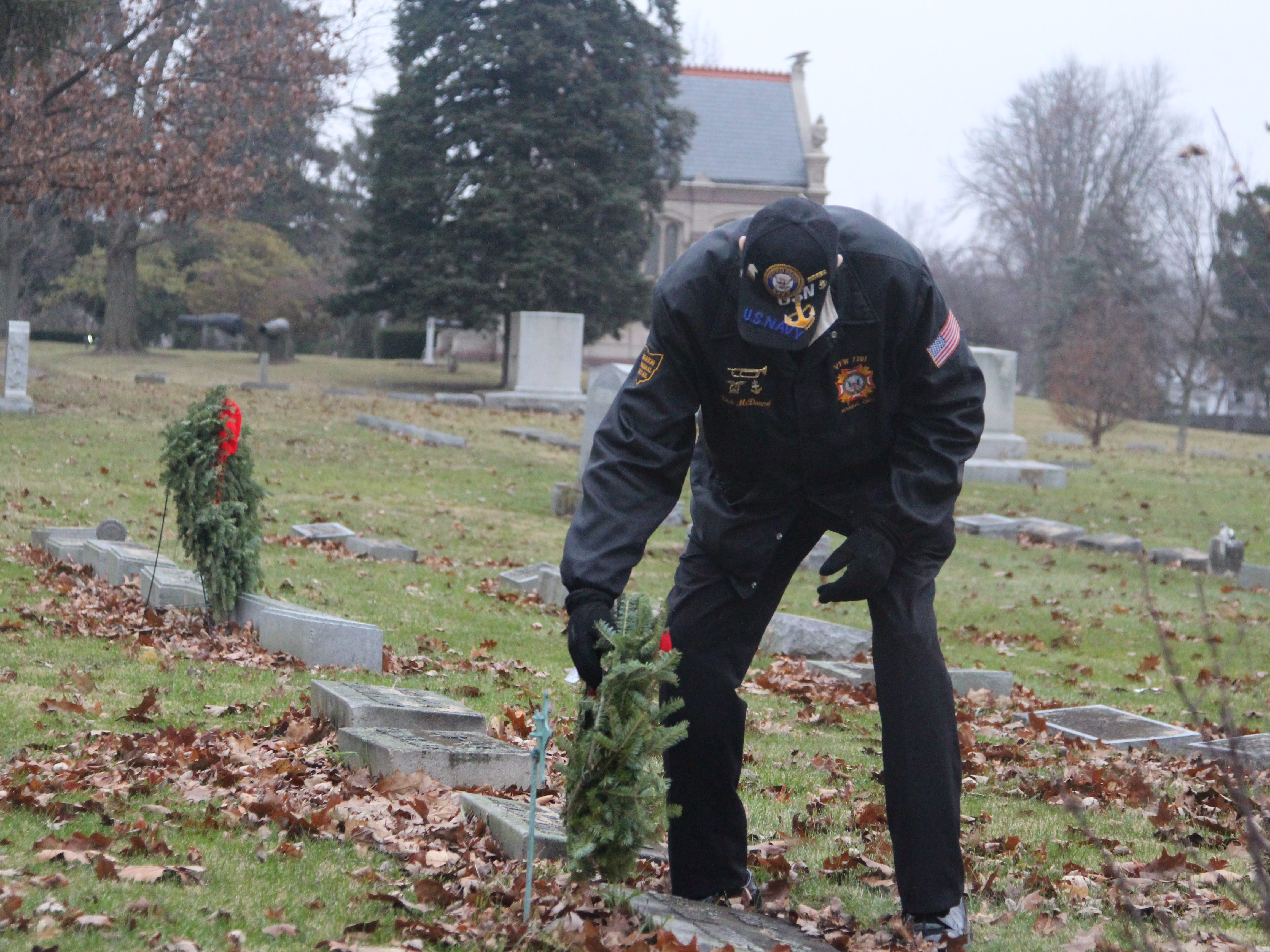 Dick McDannel, a veteran of the Korean War, lays wreaths at the graves of fellow military veterans Saturday at Marion Cemetery. He was among a band of local volunteers who took part in Wreaths Across America, a nationwide effort to honor military veterans around the holidays.