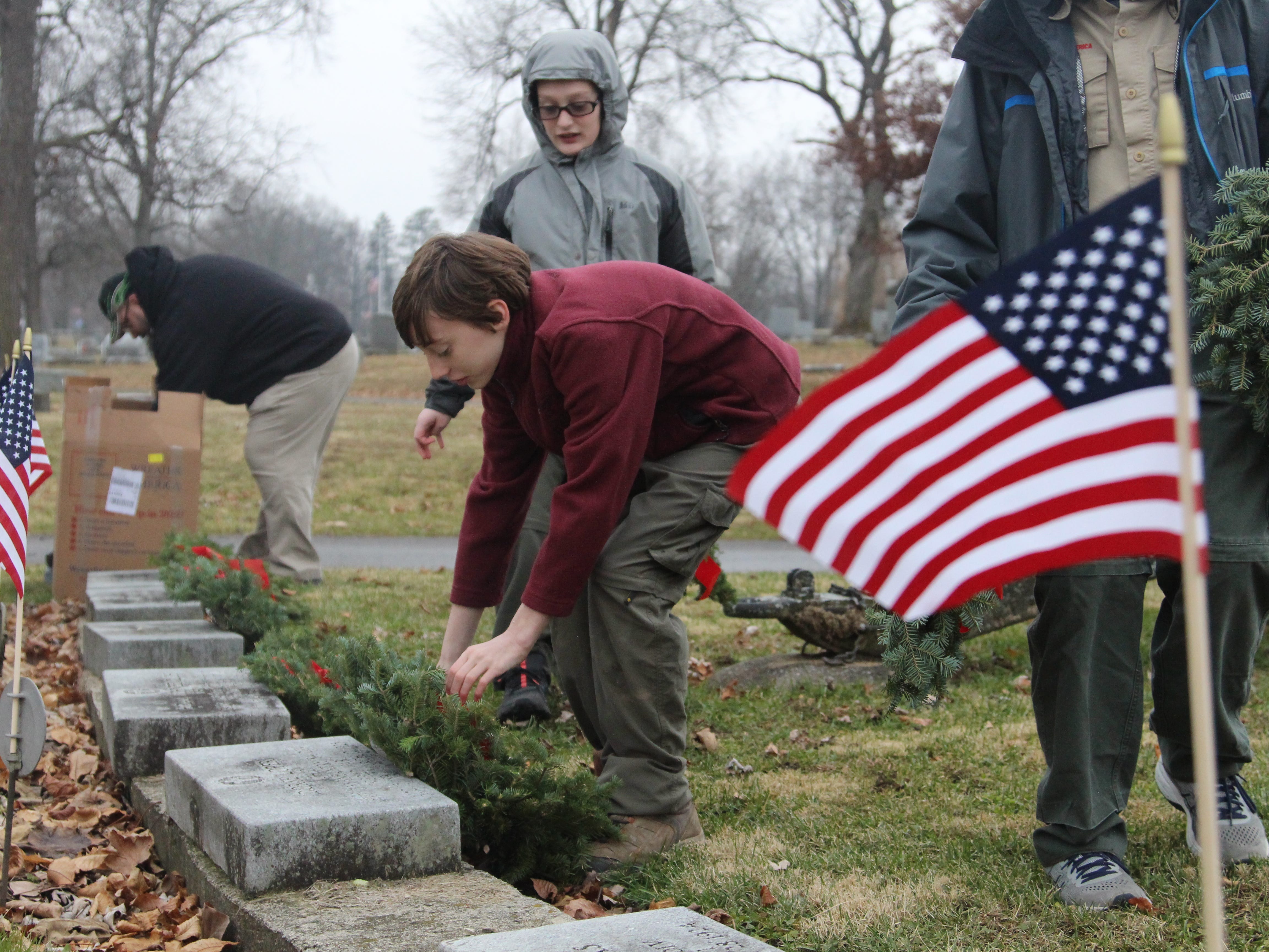 Jacob Van Voorhis, 13, lays a wreath on the grave of a military veteran Saturday at Marion Cemetery. He was one of the volunteers who took part in Wreaths Across America, a nationwide effort to honor military veterans around the holidays.