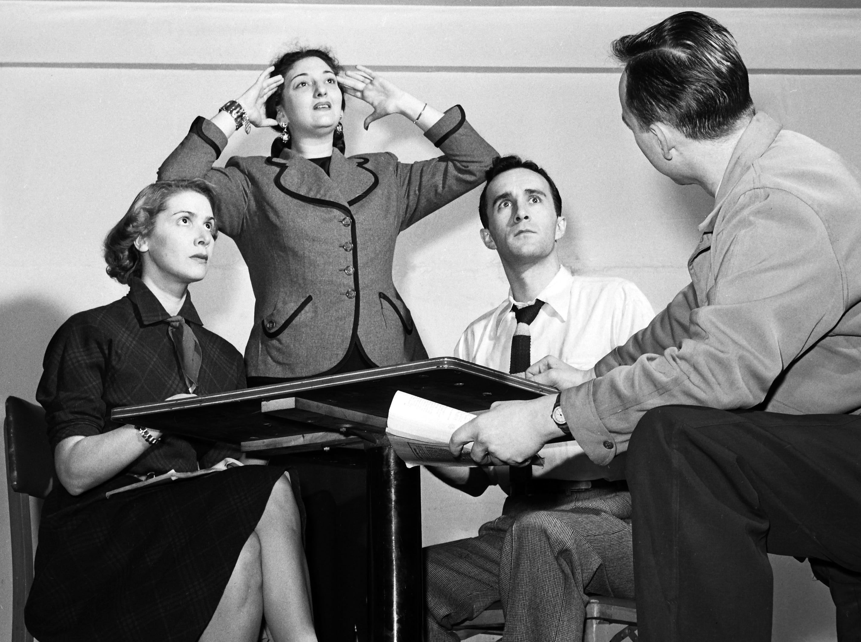 "Director Tom Fitzsimmons (Right) puts finishing touches on a seance scene from noel Coward's ""Blithe Spirit,"" which has a week's run in January 1952 at the new Arena Theatre playhouse in the basement of the King Cotton Hotel.  Rosemary Murphy, medium Carolyn Brenner and Rex Partington get rather more than they bargained for from the spirit world."