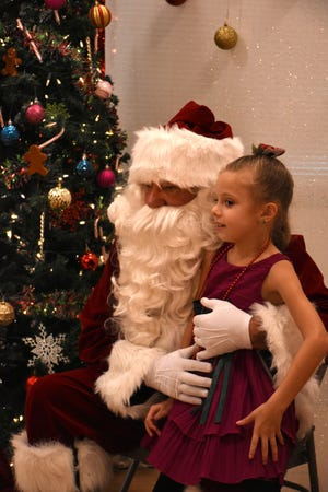 Jillian Szczepanski tells her wish list to Santa during Cookies & Milk with Santa at Mackle Park on Saturday morning.