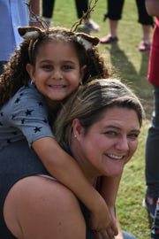 Liliana Anderson, 6, with mom Ashlee during Cookies & Milk with Santa at Mackle Park on Saturday morning.